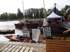 Tradycyjna Wiślana łódź płaskodenna ozdobiona zdjęciami z budowy stoi przy bulwarze na festiwalu Loary w Orleanie