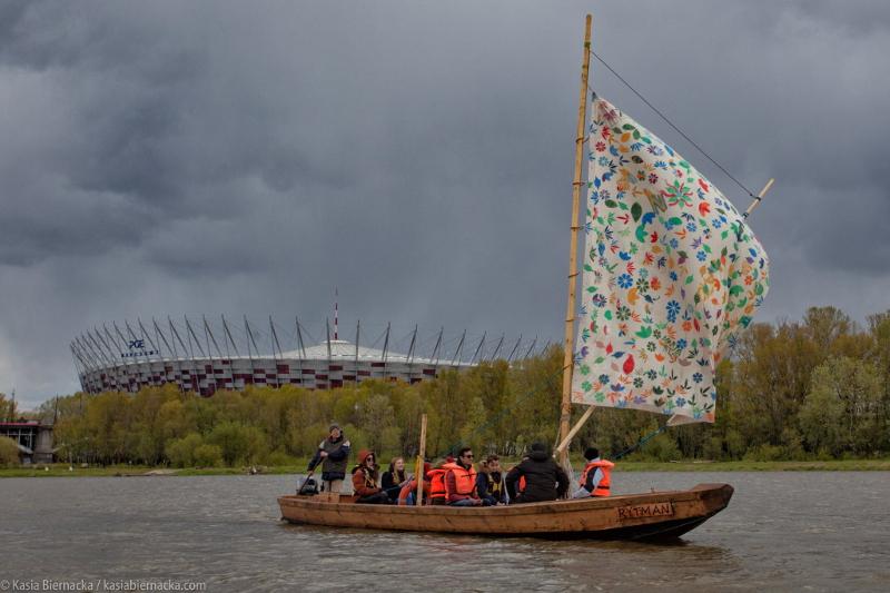 10 osób płynie drewnianą łodzią Wisła na żaglu rozprzowym. W tle widać stadion narodowy a powyżej chmury burzowe.