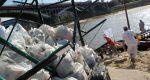 Na pierwszym planie widać górę worków śmieci na przyczepie. W tle łodzie nad Wisłą i most Poniatowskiego